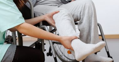 wearable device   SMA News Today   Aids   Person helping to raise leg of patient in wheelchair