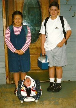 """school \ SMA News Today \ The columnist's children Katie, Matthew, and baby Jeffrey post on their first day of school in 1997. Matthew is wearing a """"No Fear"""" T-shirt."""