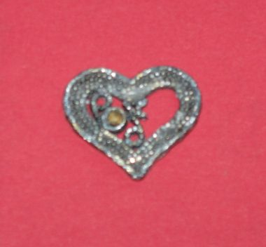 Heart Day | SMA News Today | A small silver heart charm with a gold stone in the center.